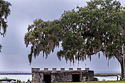 Spanish moss covers live oak trees hanging over the stone walls of the original arms magazine at the Fort Frederica National Monument, the original colonial settlement in St. Simons Island, Georgia. Fort Frederica was established by Georgia founder James Oglethorpe in 1736 to serve as a bulwark against the Spanish settlements in Florida,