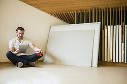 Architect sitting on floor and working on digital tablet, Bavaria, Germany