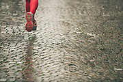 A close up of a female runner, wearing pink leggings running along a cobbled street, during the Verona Marathon on the 17th November 2019 in Verona in Italy.