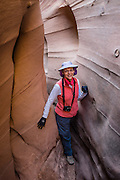 A hiker squeezes through Zebra Slot Canyon, in Grand Staircase Escalante National Monument, Utah, USA. Directions to unmarked trailhead for Zebra and Tunnel Slot Canyons: From Escalante town, drive 6 miles east on Highway 12, turn right on Hole-in-the-Rock Road, drive 7.8 miles to the third cattle guard and park on west side of road. Hike east on well-trodden but unmarked path, 5 miles round trip to Zebra Slot, plus an optional 3 miles round trip to Tunnel Slot (750 feet gain over 8 miles), using map from GSENM Visitor Center or canyoneeringusa.com. For licensing options, please inquire.