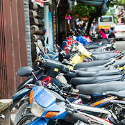 Motor scooters parked on street in Old Quarter Hanoi