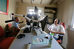 18 August. New Orleans, Louisiana.<br /> Radio NOLA HIV 102.3 LPFM.<br /> Chris Rose interviews musician Paul Sanchez on air.<br /> Photo©; Charlie Varley/varleypix.com