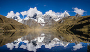 Cordillera Huayhuash reflects in Carhuacocha lake (13,600 feet) in the Andes Mountains, Peru, South America. Peaks from left to right are: Siula Grande, Yerupaja Grande (6635 m or 21,770 ft, highest point in the Amazon watershed), Yerupaja Chico, and Mount Jirishanca (Icy Beak of the Hummingbird). Day 3 of 9 days trekking around the Cordillera Huayhuash. This panorama was stitched from 5 overlapping photos.