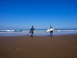 Rear view of men carrying surfboard on Sopela Beach, Biscay, Basque Country, Spain