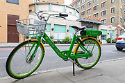 A Lime E dockless Electric Bicycle is seen on a street opposite Wapping Overground Station in east London, England on April 29, 2019. The Green pay as you ride bikes called Lime-E which are backed by Uber and Google can be found and unlocked via a mobile phone application.