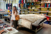 Woman looking at rugs and homeares, Calma Chica boutique, Palermo, Buenos Aires, Federal District, Argentina.