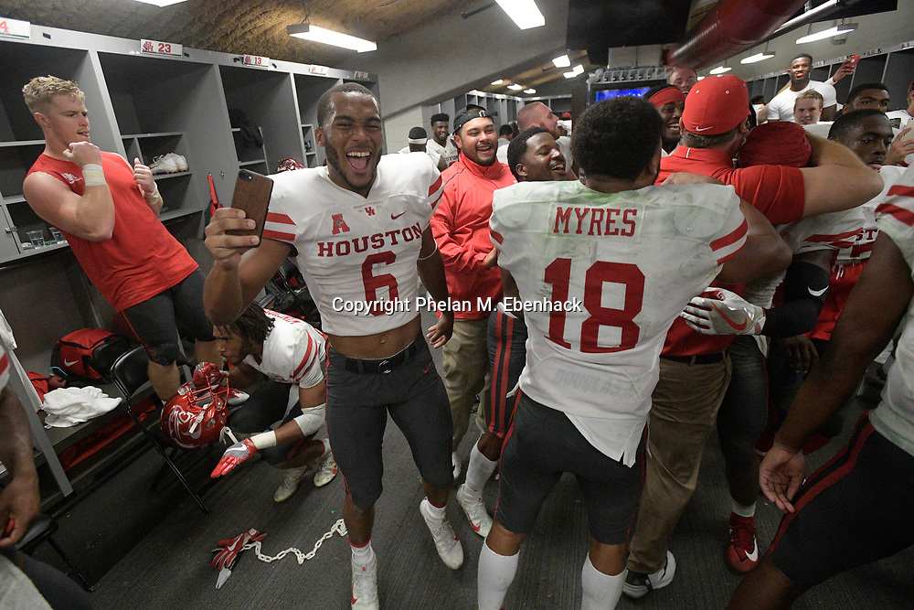 Houston defensive back Khari Dotson (6) and cornerback Alexander Myres (18) celebrate with teammates in the locker room after an NCAA college football game against South Florida Saturday, Oct. 28, 2017, in Tampa, Fla. Houston won 28-24. (Photo by Phelan M. Ebenhack)