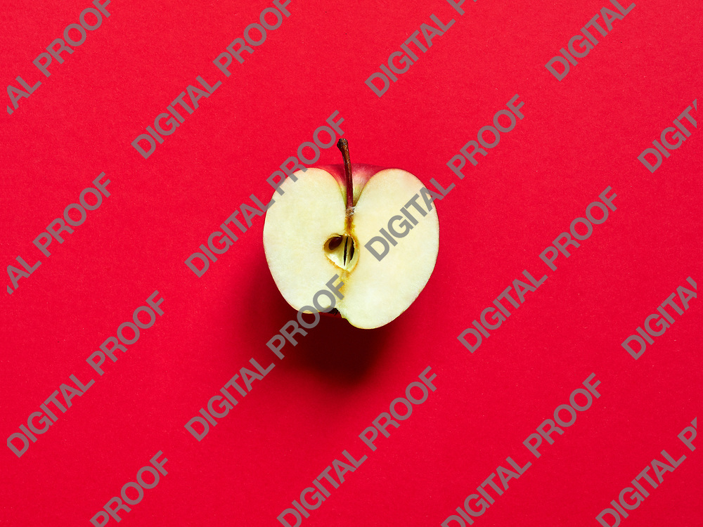Apple fruit sliced by half isolated in studio over a vivid red background