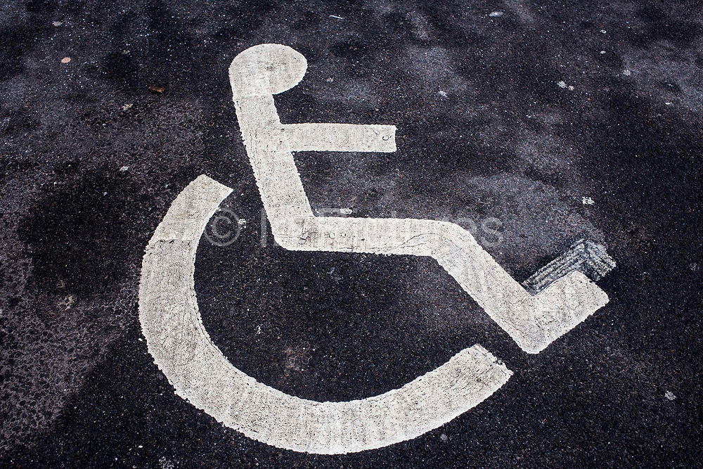 Wheelchair figure stenciled in white lines on tarmac as a sign for a disabled parking bay Middlesborough, England, UK.