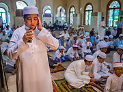 10 APRIL 2015 - BANGKOK, THAILAND: A Thai Muslim teenager recites the call to prayer at Masjid Ton Son in Bangkok before Friday prayers. (Masjid is the Thai word for Mosque.) A Pew Research Center study recently released identified Islam as the fastest growing religion in the world. Masjid Ton Son was the first mosque in Bangkok, founded in 1688 during the reign of King Narai, of the Ayutthaya era. Muslims are about 5 percent of Thailand, but make up a bigger proportion of Bangkok. Thailand's deep south provinces are Muslim majority.    PHOTO BY JACK KURTZ