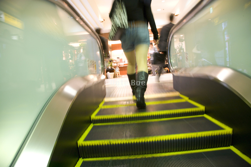female person stepping off the escalator