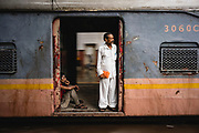 Two men look out of an open train doorway as their train departs Mumbai's Chhatrapati Shivaji Terminus station, Chhatrapati Shivaji Terminus (CST), Mumbai, India