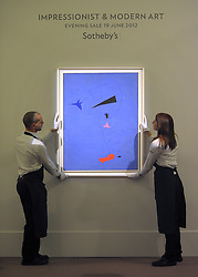 """© Licensed to London News Pictures. 14/06/2012. London, UK Gallery technicians hold Joan Miro's painting """"Peinture' which is estimated to fetch 15-20MillionGBP. Photocall for Sotheby's June Impressionist and Modern Art Sale this June. Photo credit : Stephen Simpson/LNP"""