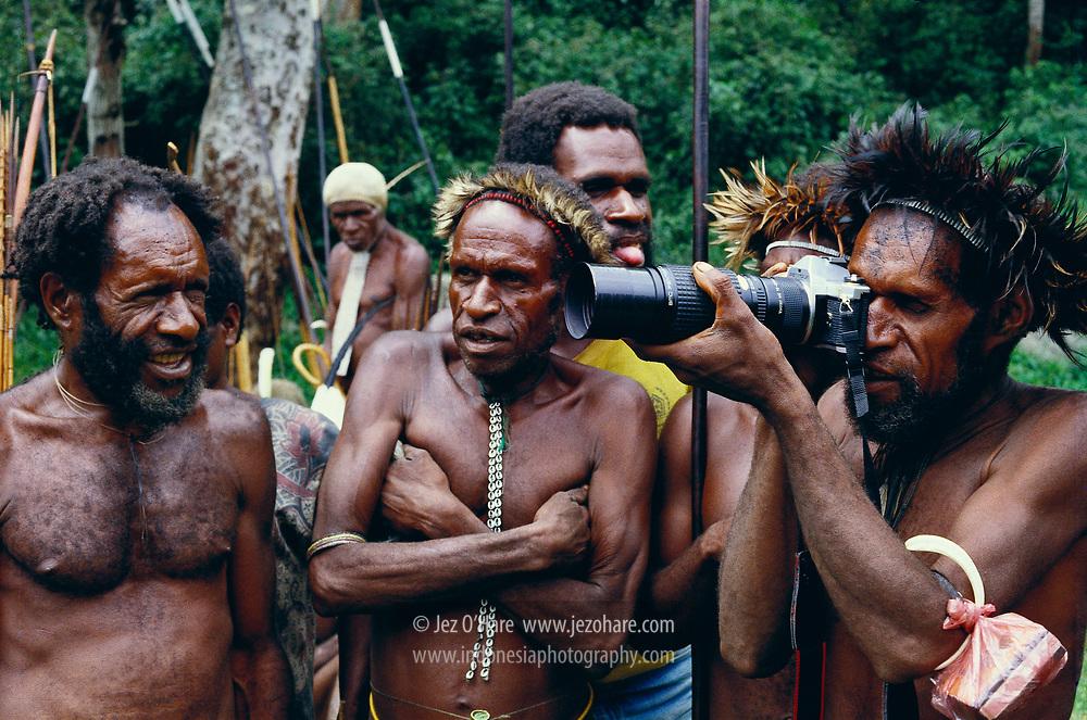 Dani tribesmen of Hetigima village eyeing their enemy during a war with Kurima village in 1987. Southern Baliem Valley, Papua, Indonesia.