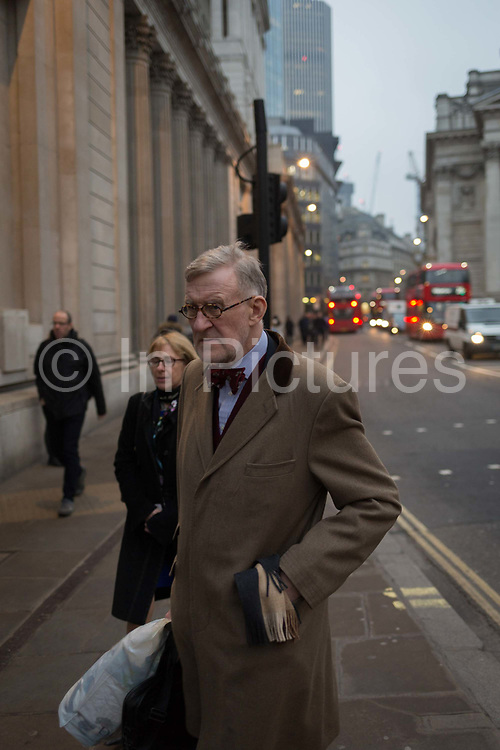 An elderly gentleman wearing a bow tie walks past the Bank of England, in the Square Mile, the capitals oldest district and financial centre, on 9th February 2017, in the City of London, England. Traditional City bowler hats and pinstripe suits are now rare, even among older bankers and financiers.