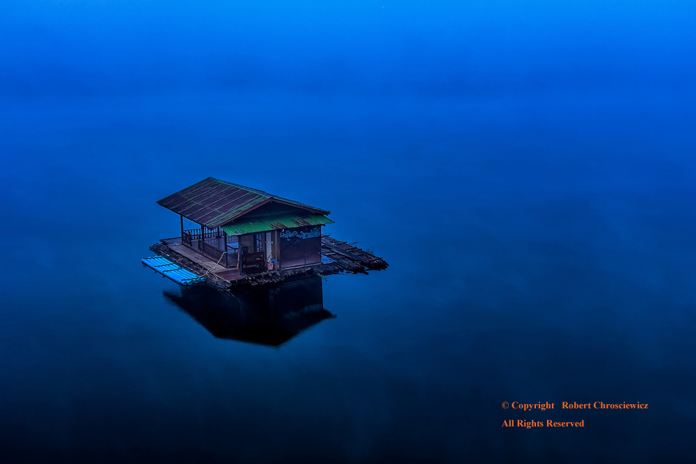 Home Amongst the Fog: Seen from on high, a lone house boat floats in amongst the early morning fog on the still waters of Khao Laem Reservoir, Sangkhlaburi Thailand.