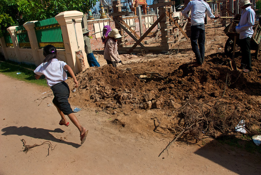 A young girl runs past a construction site adjacent to her primary school during her lunch break in the village at the base of Phnom Krom just outside of Siem Reap, Cambodia.