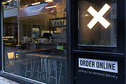 A cross is illuminated outside a coffee bar that, when open, serves online orders from its hatch, during the third lockdown of the Coronavirus pandemic, in the 'City of London', the capital's financial district, aka The Square Mile, on 2nd February 2021, in London, England.
