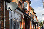 Satellite dishes outside terraced homes for Sky TV. With television now completely digital in the UK, the satellite dish is an increasingly common site.