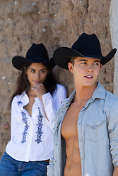 cowboy and woman wearing a cowboy hat outdoors against an adobe wall in New Mexico