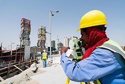 Construction worker using theodolite at Lusail City new property development in Doha, Qatar