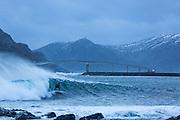 Bad weather ia good weather for surfers. Here at Runde, Norway, with the Runde bridge in the background | Dårlig vær er godt vær for surfere. Her på Runde, med Rundebrua i bakgrunnen.