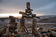 A stone marker (inukshuk) sits on the crest of a hill above Iqaluit in Nunavut, Canada. (From the book What I Eat: Around the World in 80 Diets.)  These traditional Inuit stone markers are built to serve as landmarks in permafrost areas where there are no trees or other distinctive features. In the distance, a taxi climbs the grade on the Road to Nowhere, so named because Iqaluit isn't connected by road to the mainland?or to other parts of Baffin Island.