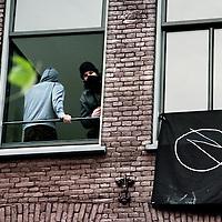 """Nederland, Amsterdam , 7 december 2009..Krakers van de  kraakgroep """"Dappersociaal"""" kijken vanuit de ramen van een gekraakte te koop staande voormalige sociale huurwoningen   aan de Pieter Vlamingstraat..Foto:Jean-Pierre Jans"""