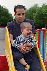 Young boy sitting on father's lap crying at top of slide in children's playground,