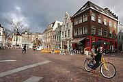 Een meisje op de OV-fiets steekt de paraplu op bij een donkere lucht op de Korte Minrebroederstraat in Utrecht.<br /> <br /> A girl on a rental bike is putting up the umbrella when the sky is dark.