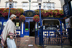 © Licensed to London News Pictures. 16/10/2020. London, UK. A woman wearing a face covering walks past a JD Weatherspoon's pub, 'The Toll Gate', in north London. The pub chain announced a £95m annual pre-tax loss, its first since 1984 due to the coronavirus lockdown restrictions on the pub industry. Yesterday, the government announced that from midnight tonight, households in London will not be allowed to mix indoors, including in pubs and restaurants, as London moves into Tier 2 COVID-19 restrictions. Photo credit: Dinendra Haria/LNP
