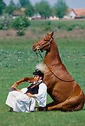 Hungarian Csikos cowboy showing horsemanship skills with horse on The Great Plain of Hungary  at Bugac, Hungary