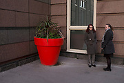 People on the streets interract with a large red plant pot in the City of London, UK. This situation creates a weird scale to this street scene.