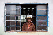 Middle aged Guarani man standing in the prison he was locked in due to land conflicts. The Guarani are one of the most populous indigenous populations in Brazil, but with the least amount of land. They mostly live in the State of Mato Grosso do Sul and Mato Grosso. Their tradtional way of life and ancestral land is increasingly at risk from large scale agribusiness and agriculture. There have been recorded cases and allegations of violence between owners of large farms and the Guarani communities in this region.