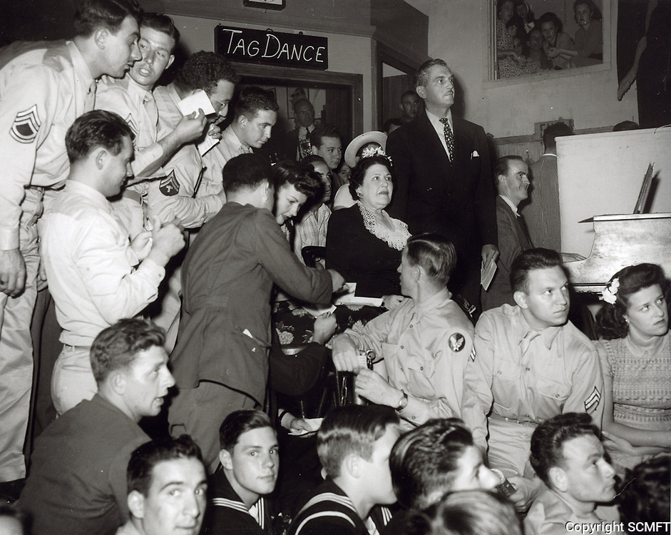 1943 Unknown actress signing autographs and Louella Parsons at the Hollywood Canteen