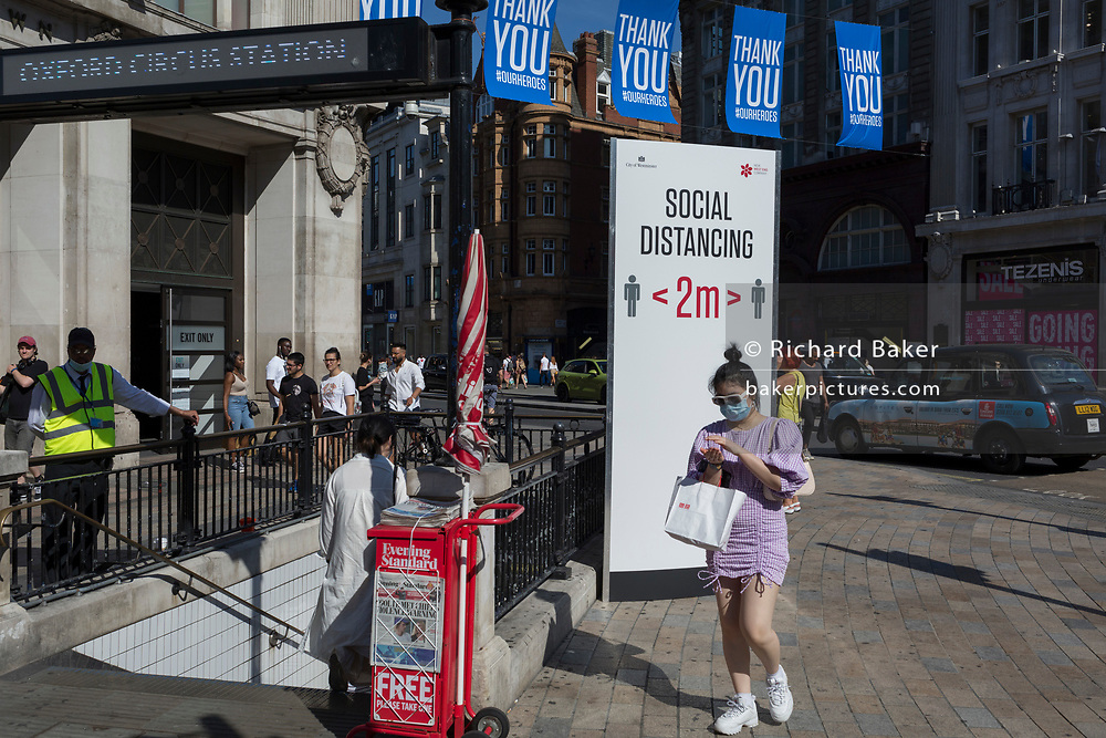 With a further 184 reported UK Covid deaths in the last 24 hrs, a total now of 43,414, a shopper rubs sanitiser gel into her hands while passing through Oxford Circus where a post advises Londoners to observe the correct two metre social distances, during the Covid pandemnic lockdown, now easing after three months of the Stay At Home policy but now being relaxed as the shops re-open, on 26th June 2020, in London, England. Government restrictions on the 2 metre rule is to be realxed on 4th July and replaced with 'one metre plus' in the hope it stimulates the struggling UK economy.