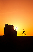 Randy Wells Southwest lifestyle photography, Image of woman running at sunrise at Monument Valley Navajo Tribal Park with Mittens and buttes, Arizona and Utah, American Southwest, model released