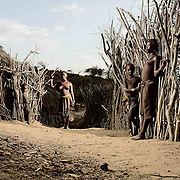 """Daina Gele, Goba Gele, Moodu Bora and Dobo Eike in their village at sunset.<br /> <br /> Hamer live in villages dotted with small clusters of traditional wooden and mud huts. Family members always live within the same cluster.<br /> <br /> The huts are always constructed the same way and the same size irrespective of the wealth of the family.<br /> <br /> When I asked why they made huts so small that were difficult to enter and where you could not stand upright...one Hamer replied """"it's our tradition and culture""""."""