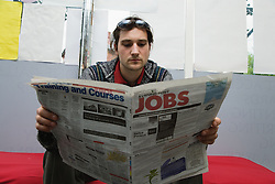 Czech man looking in the job section of the newspaper for work,