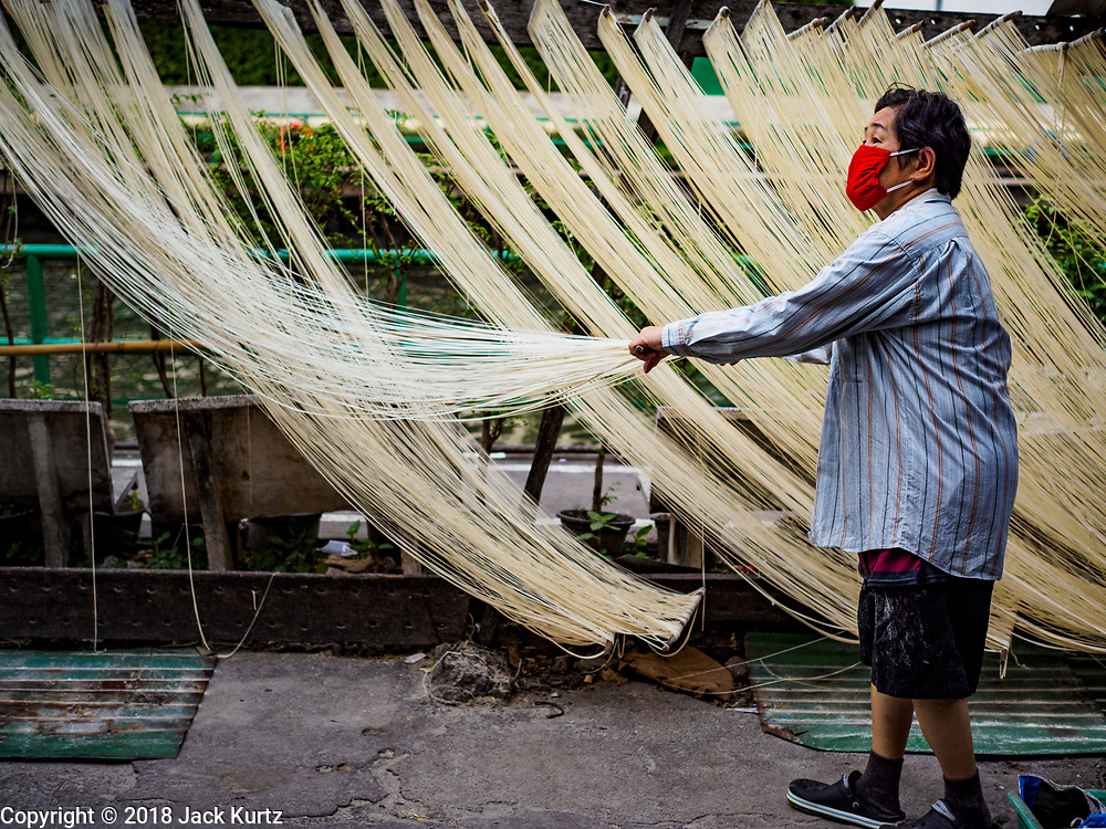 """29 DECEMBER 2018 - BANGKOK, THAILAND: A woman stretches longevity noodles during the drying process in front of her family shophouse. The family has been making traditional """"mee sua"""" noodles, also called """"longevity noodles"""" for three generations in their home in central Bangkok. They use a recipe brought to Thailand from China. Longevity noodles are thought to contribute to a long and healthy life and  are served on special occasions, especially Chinese New Year, which is February 4, 2019. These noodles were being made for Chinese New Year.     PHOTO BY JACK KURTZ"""