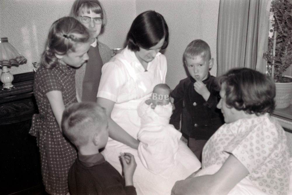 nurse showing newborn baby to the mother surrounded by the other children 1960s
