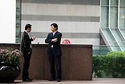 Businessmen chat at the Bank of China office, in the financial district of Hong Kong, China
