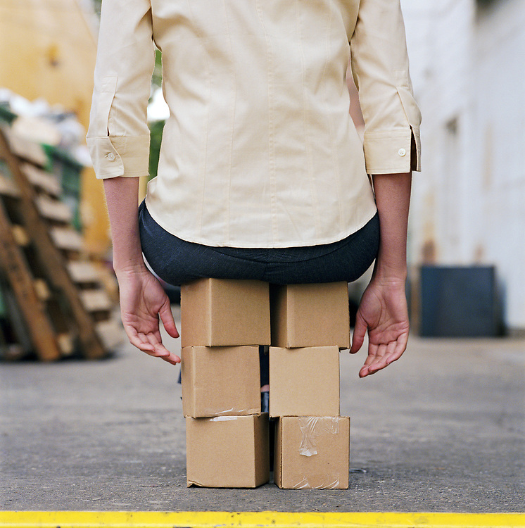 Young woman sitting on stack of small boxes, rear view