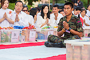 20 OCTOBER 2012 - BANGKOK, THAILAND: Thai soldiers and members of the public pray at a special alms giving ceremony in Bangkok. More than 2,600 Buddhist Monks from across Bangkok and thousands of devout Thai Buddhists attended the mass alms giving ceremony in Benjasiri Park in Bangkok Saturday morning. The ceremony was to raise food and cash donations for Buddhist temples in Thailand's violence plagued southern provinces. Because of an ongoing long running insurgency by Muslim separatists many Buddhist monks in Pattani, Narathiwat and Yala, Thailand's three Muslim majority provinces, can't leave their temples without military escorts. Monks have been targeted by Muslim extremists because, in the view of the extremists, they represent the Thai state.          PHOTO BY JACK KURTZ