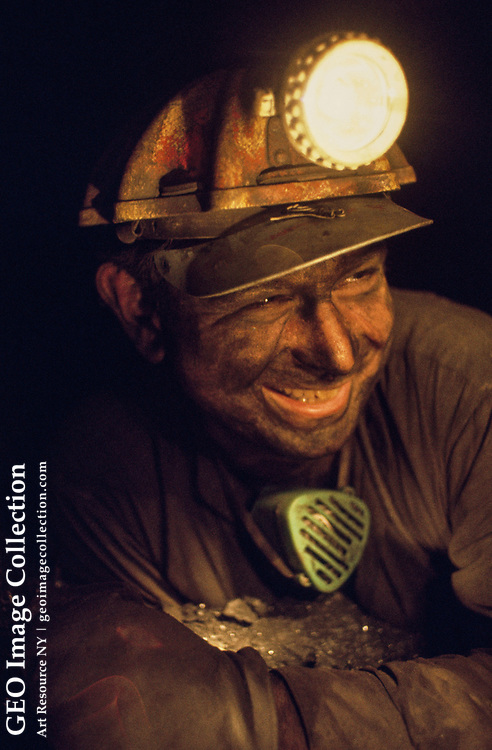A coal miner tunnels into a shallow seam underground.