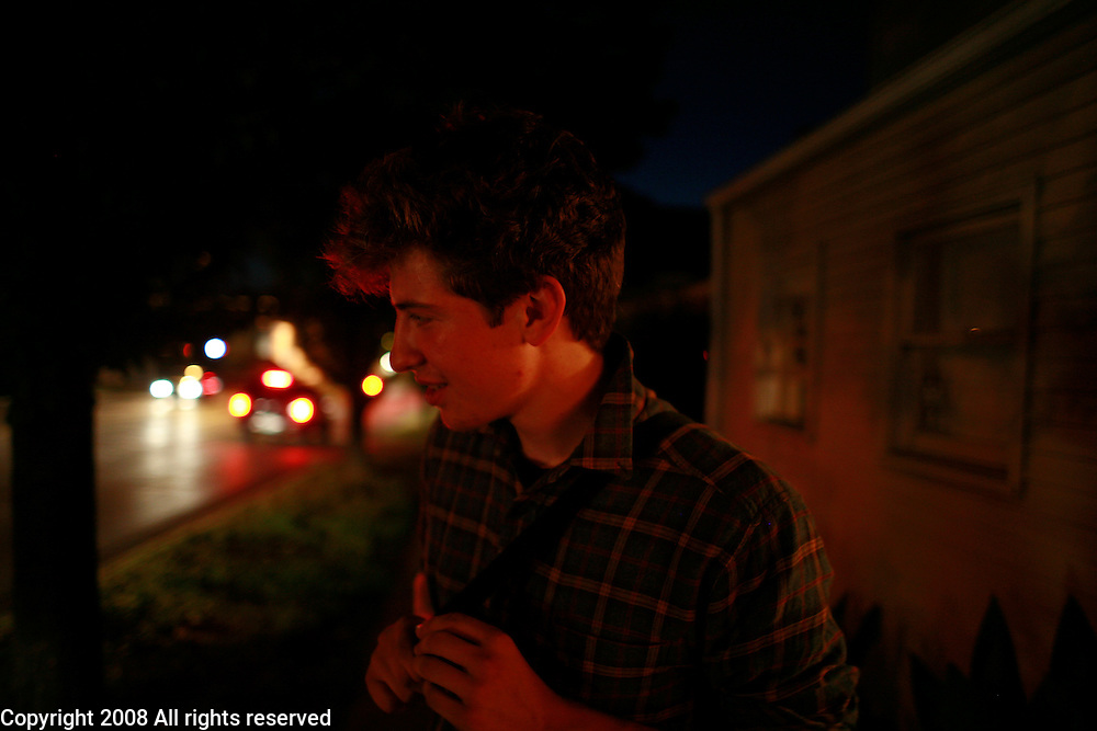 A traveling folk singer hangs out on a sidewalk at dusk after playing a show for a small group of artist, punk rockers and youth in the gallery at Sweet Hickory in Bloomington, Ind.