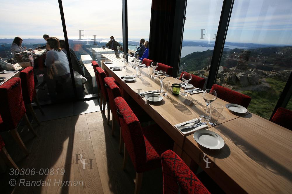 Picture windows and long tables in restaurant atop Mount Ulriken afford dinner patrons unobstructed vistas of Bergen, Norway.