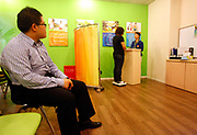 Simon Wang watches fellow dieter Wu Yu'e weigh in before beginning their class at the WeightWatchers center in Shanghai, China on 12 May 2010.  An increasing number of Chinese people, especially those who live in cities, are becoming obese due to high caloric and protein diet, a problem that is almost unheard of just a generation ago.