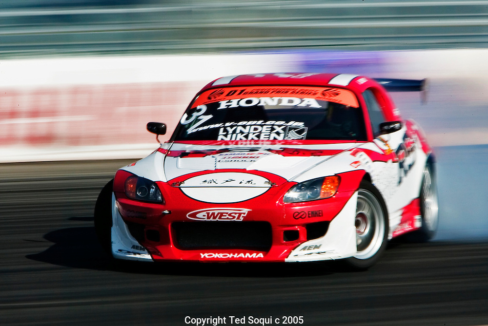 A Drift car in a controlled skid at around 100mph..Drift racing visits Irwindale Motor Speedway. Drift racing originated in Japan and is becoming very popular in the USA. The drivers are rated on their driving style. They must maintain control of their cars while driving them in a constant state of skid/burnout at around 100mph on a road course track. The cars are production cars with some modifications and are usually street legal..Irwindale Motor Speedway, CA USA .2/27/05.Photo by Ted Soqui c 2005