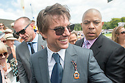 © Licensed to London News Pictures. 31/07/2014. Chichester, UK. Hollywood actor Tom Cruise signs autographs as he walks through racegoers.  Ladies Day at Glorious Goodwood at Goodwood racecourse in Chichester today 31/07/14. Photo credit : Stephen Simpson/LNP